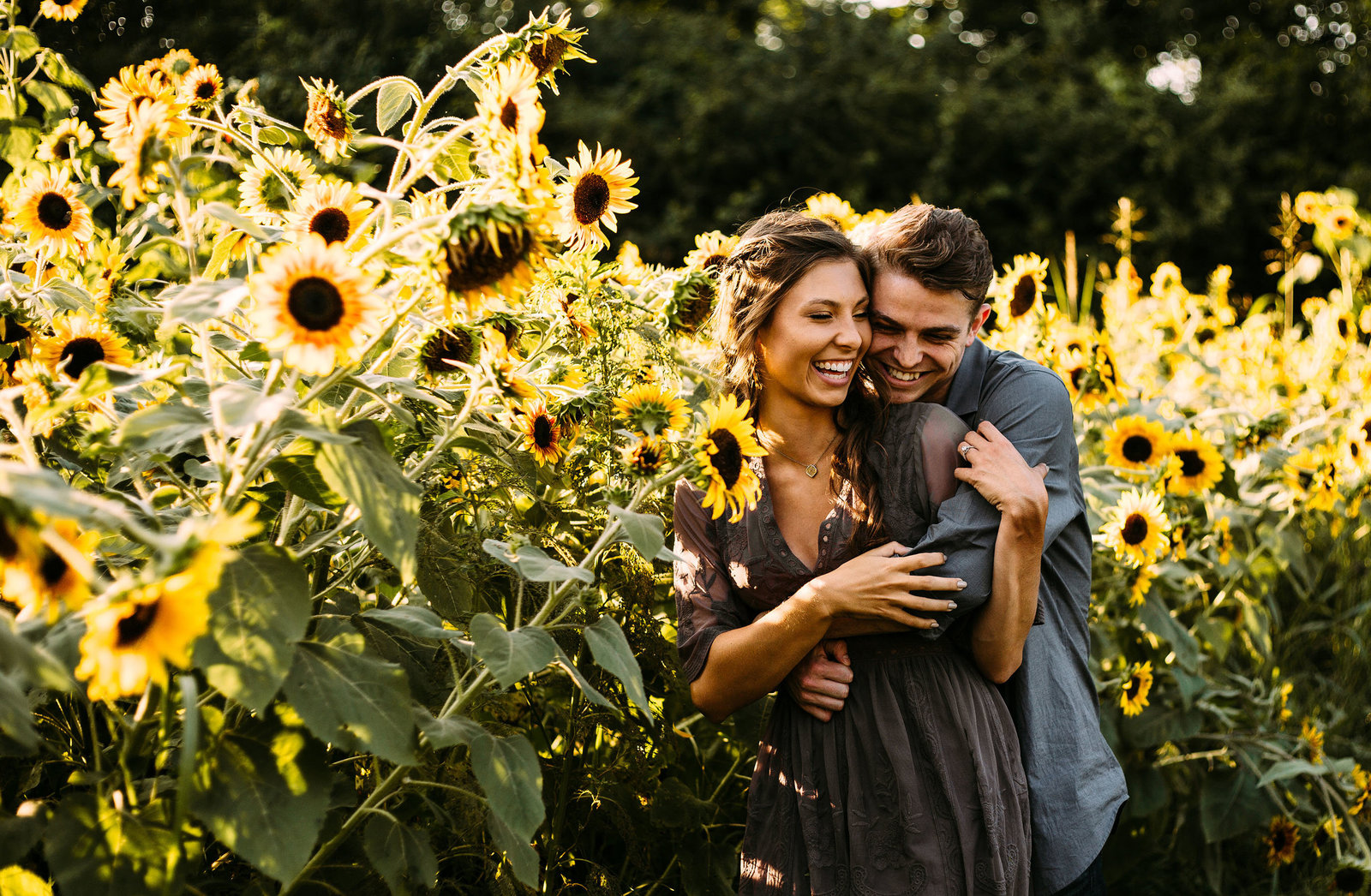 Engaged couple laughing in sunflower field in Murfreesboro