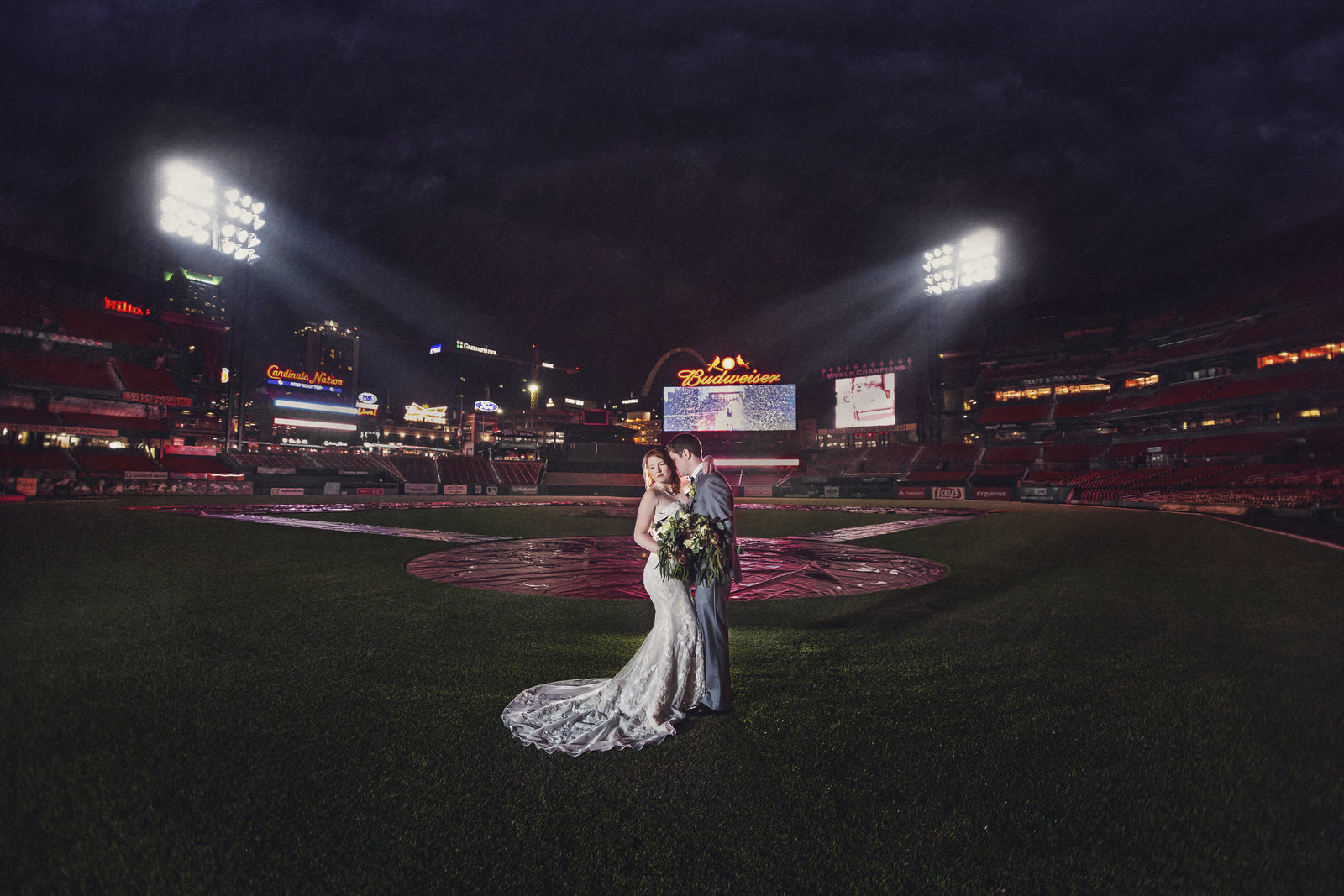 Bride and Groom, Kailyn and Adam, pose on the field of Busch Stadium as the field lights illuminate them by Jackelynn Noel Photography