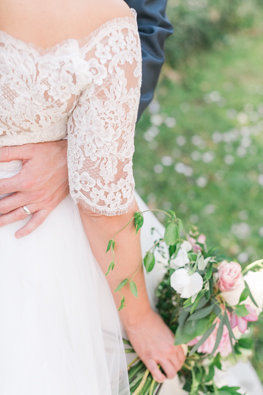 Husband wraps his hands around wife's waist while she lightly grasps her bouquet