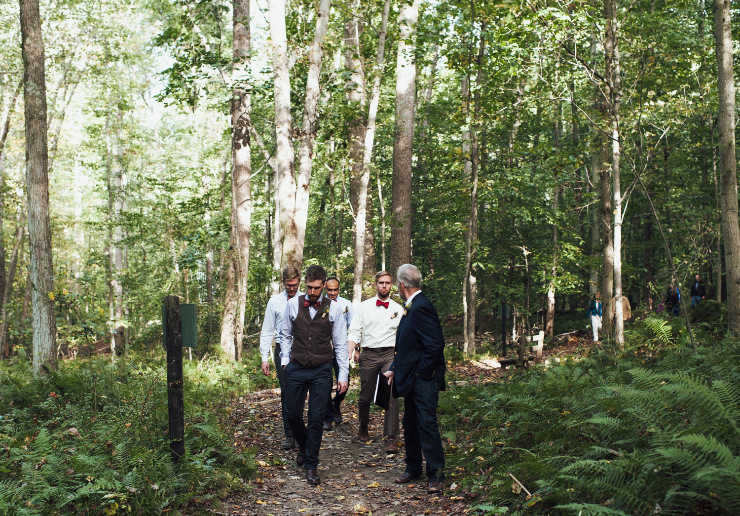 groomsmen walking to wedding ceremony at rustic camp wedding