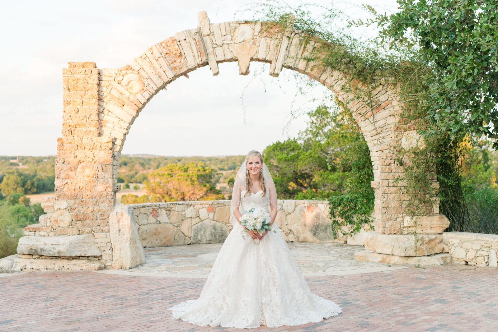 Bride stands under arch at Ian's Chapel of Camp Lucy in Dripping Springs