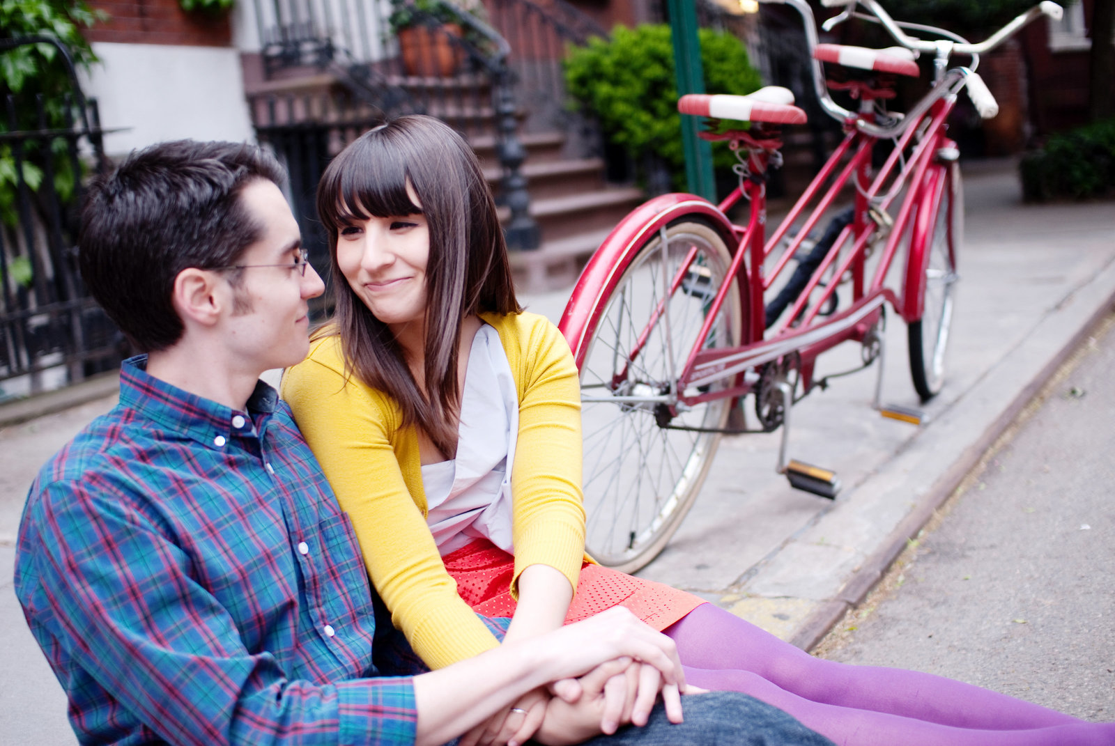an engaged couple in colorful clothes sit on the sidewalk in front of a tandem bike