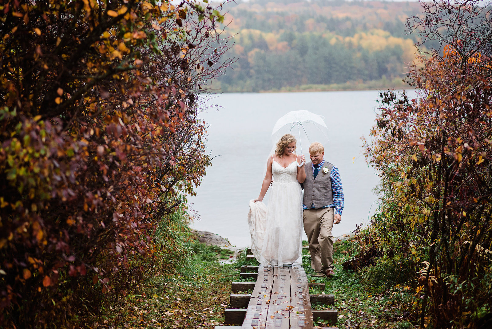 rainy wedding photos, bride and groom in the rain, clear umbrella wedding, fall wedding in Vermont, bride and groom at a lake