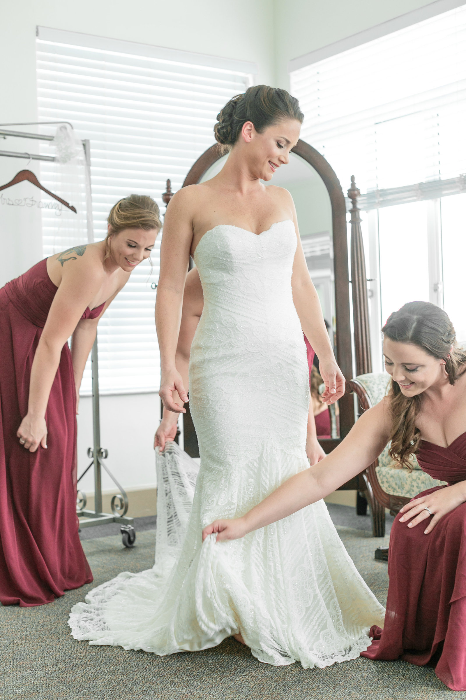 Bridesmaids fixing the bride dress at mansion of tuckahoe