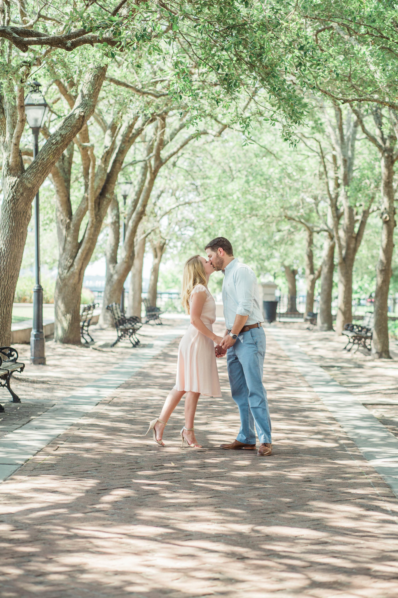 Engaged couple stroll down path under trees at the waterfront park, Downtown Charleston, South Carolina