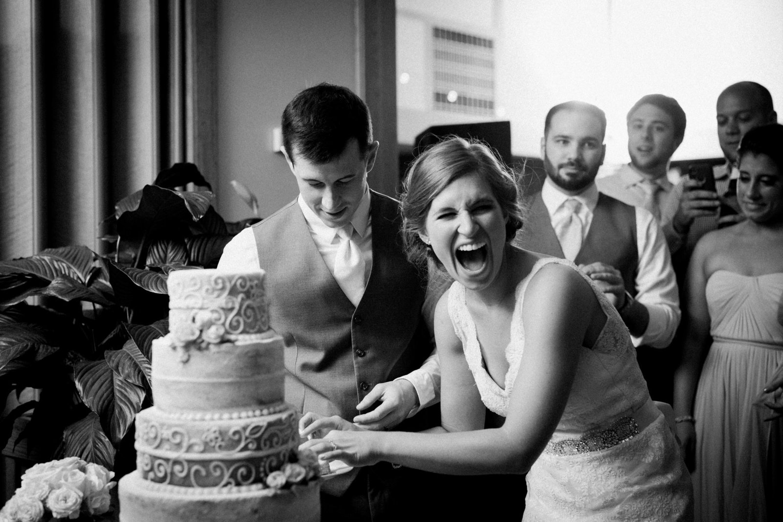 a bride laughs while cutting her wedding cake at winterthur gandens wedding