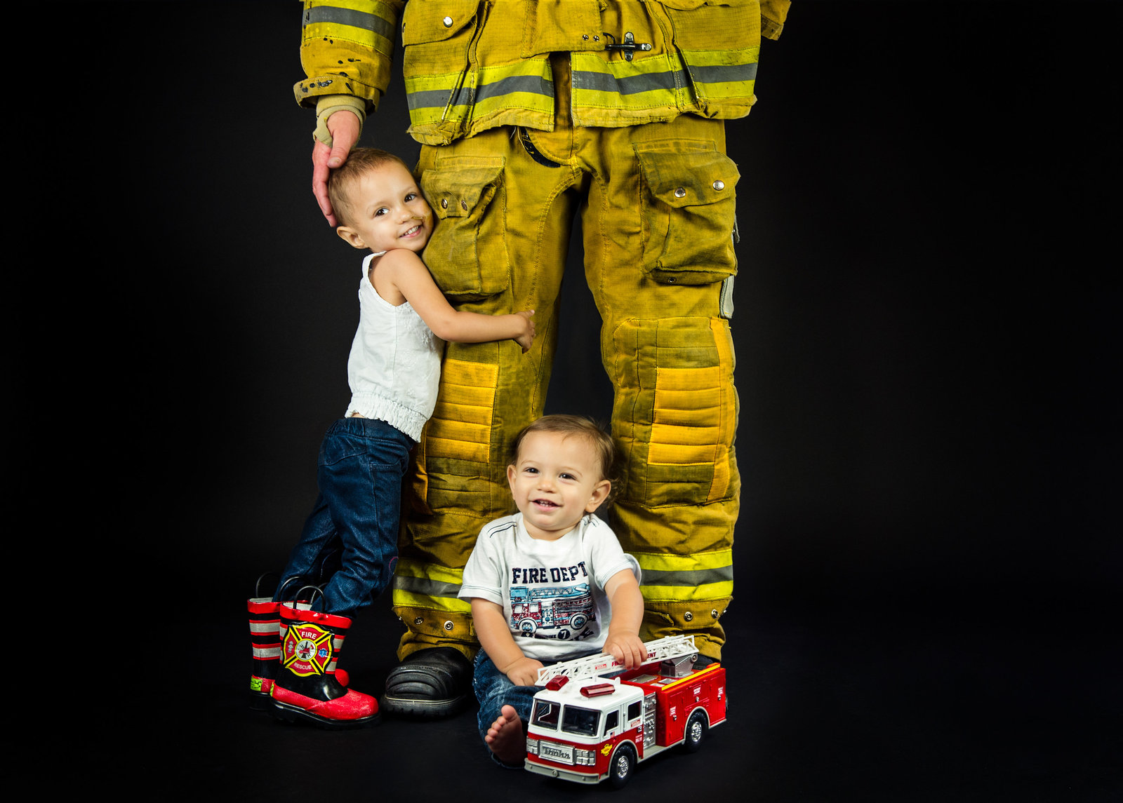 children with dad in fireman gear with toy fire truck and boots