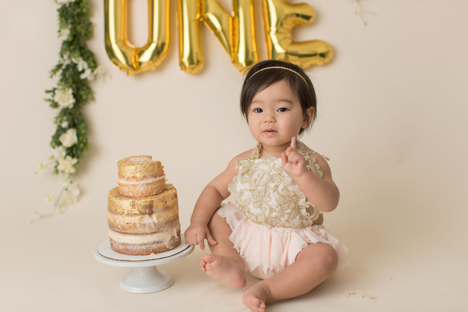 one year old with gold balloons