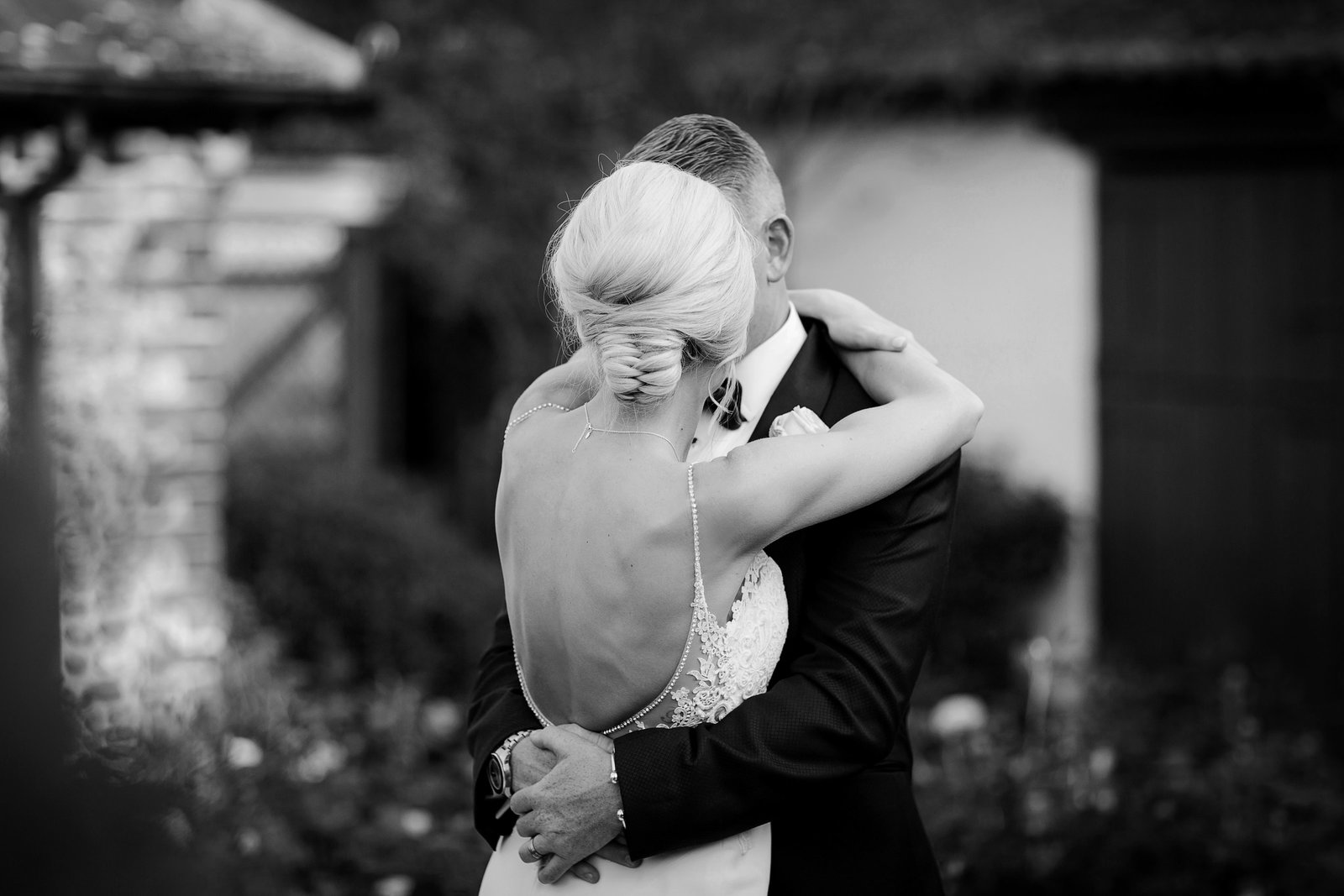 Black and white photograph of bride and groom hugging it out at Southend Barns while bride wears an Enzoani dress and her hair in a wow plaited bun and groom wears black tie.