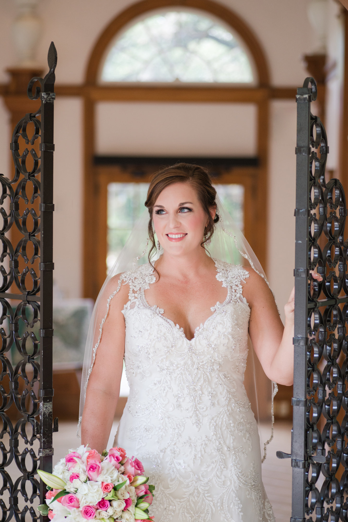 Bride wearing Maggie Sottero Gown holds on to iron gate in Driscoll room of Laguna Gloria in Austin, Texas holding pink and white bouquet