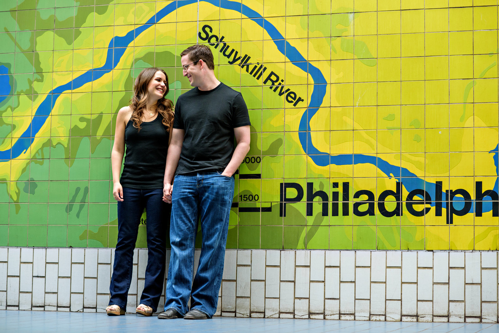 A couple in love in front of a philadelphia mural in the subway.