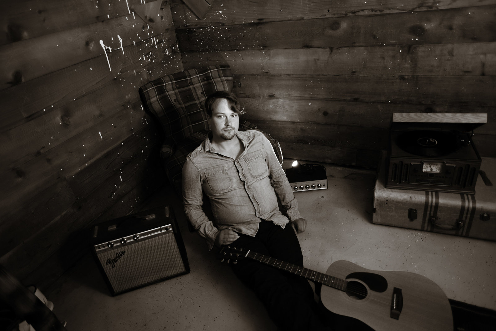 mikael pederson sits in his basement surrounded by his guitar and amps