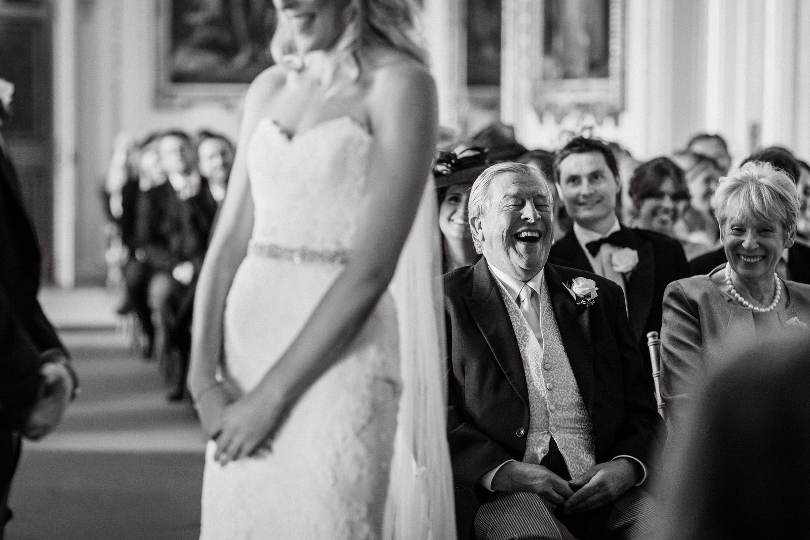 Black and white wedding photography at Goodwood House of the bride blurred in the foreground and the father of the bride behind laughing with emotion during the ceremony