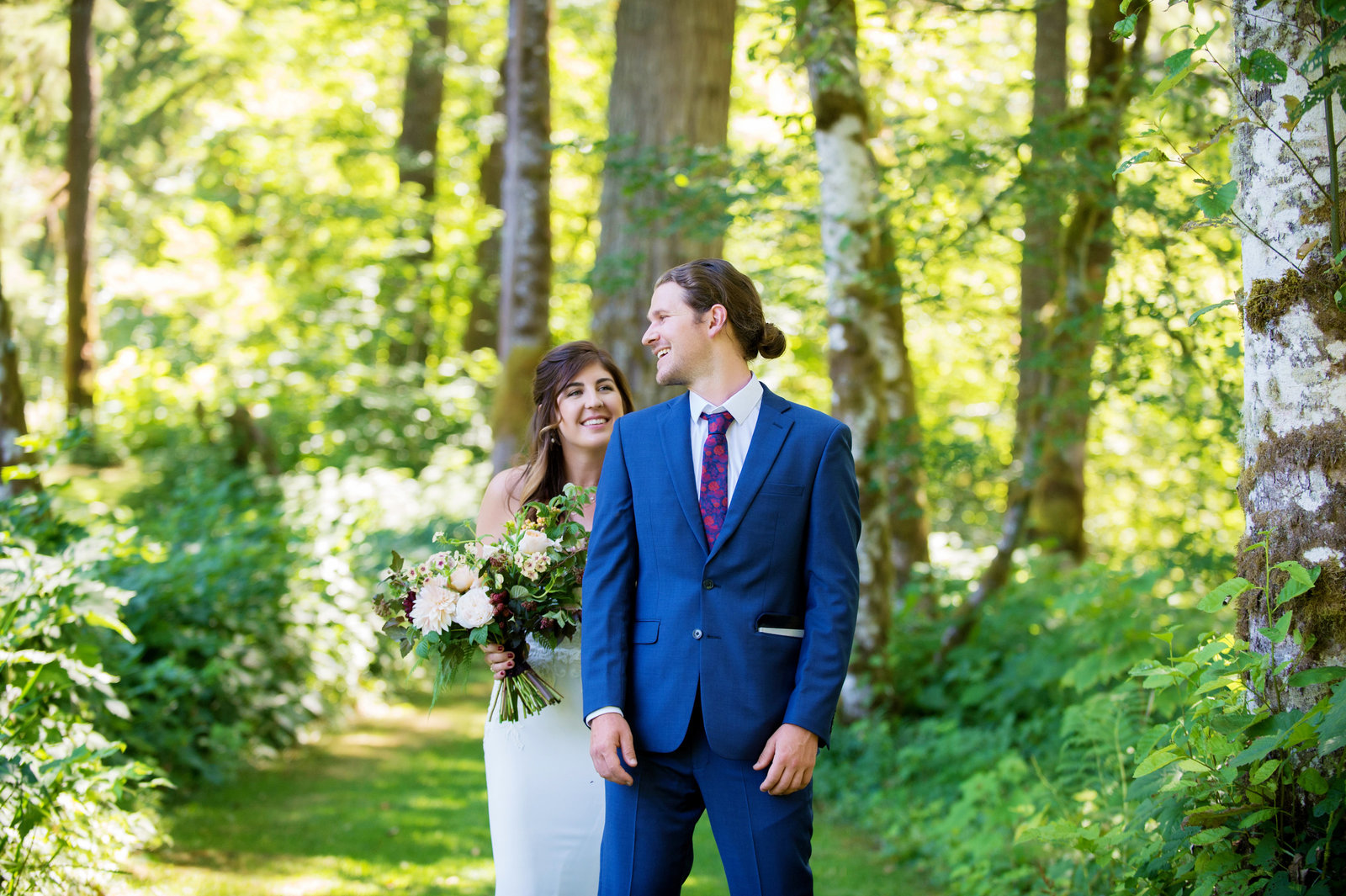 bride sneaks up behind groom on a wooded trail for the first look