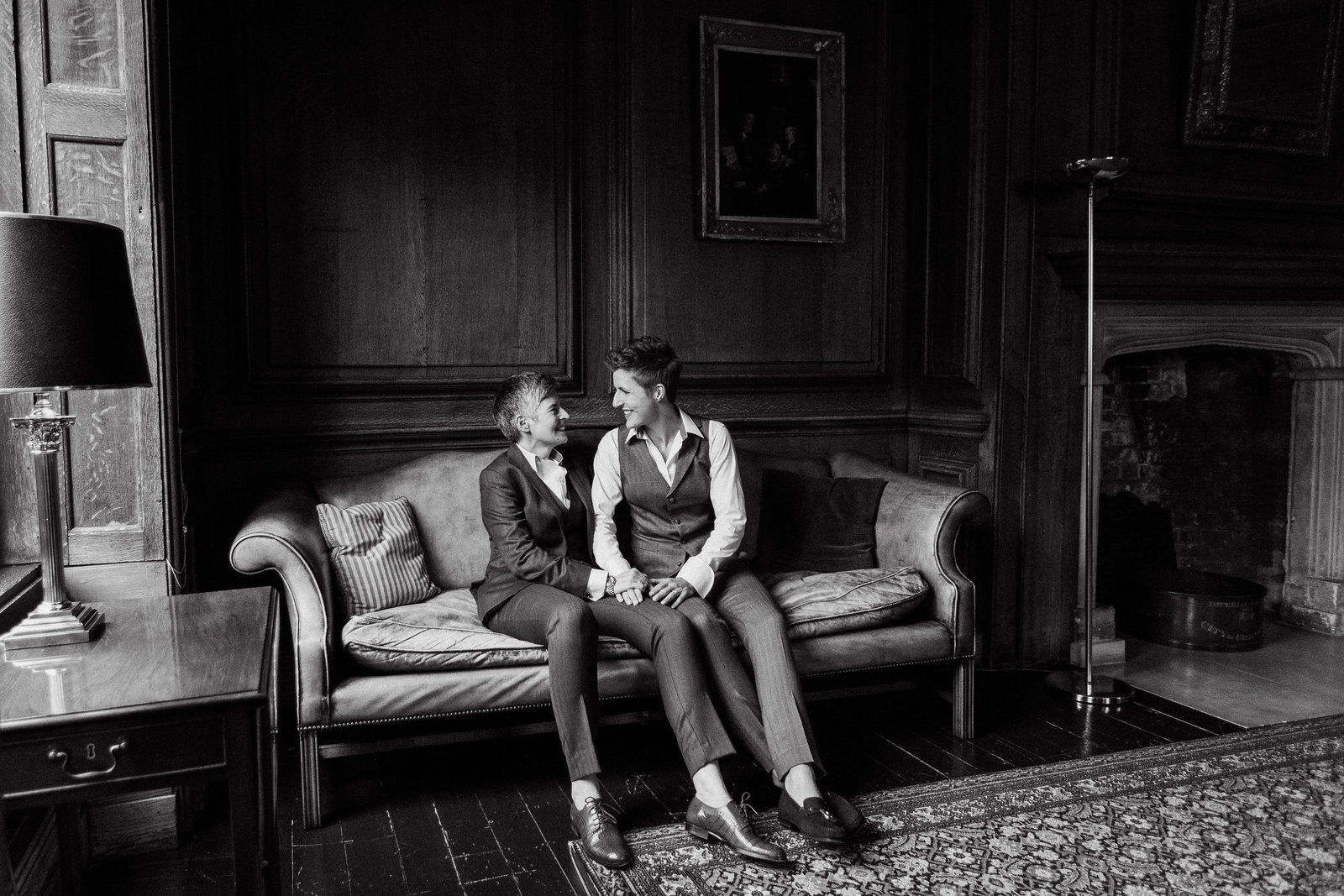 Same sex wedding photo of these two beautiful brides at Edes House in Chichester, sat on the vintage leather sofa wearing Gresham  Blake suits