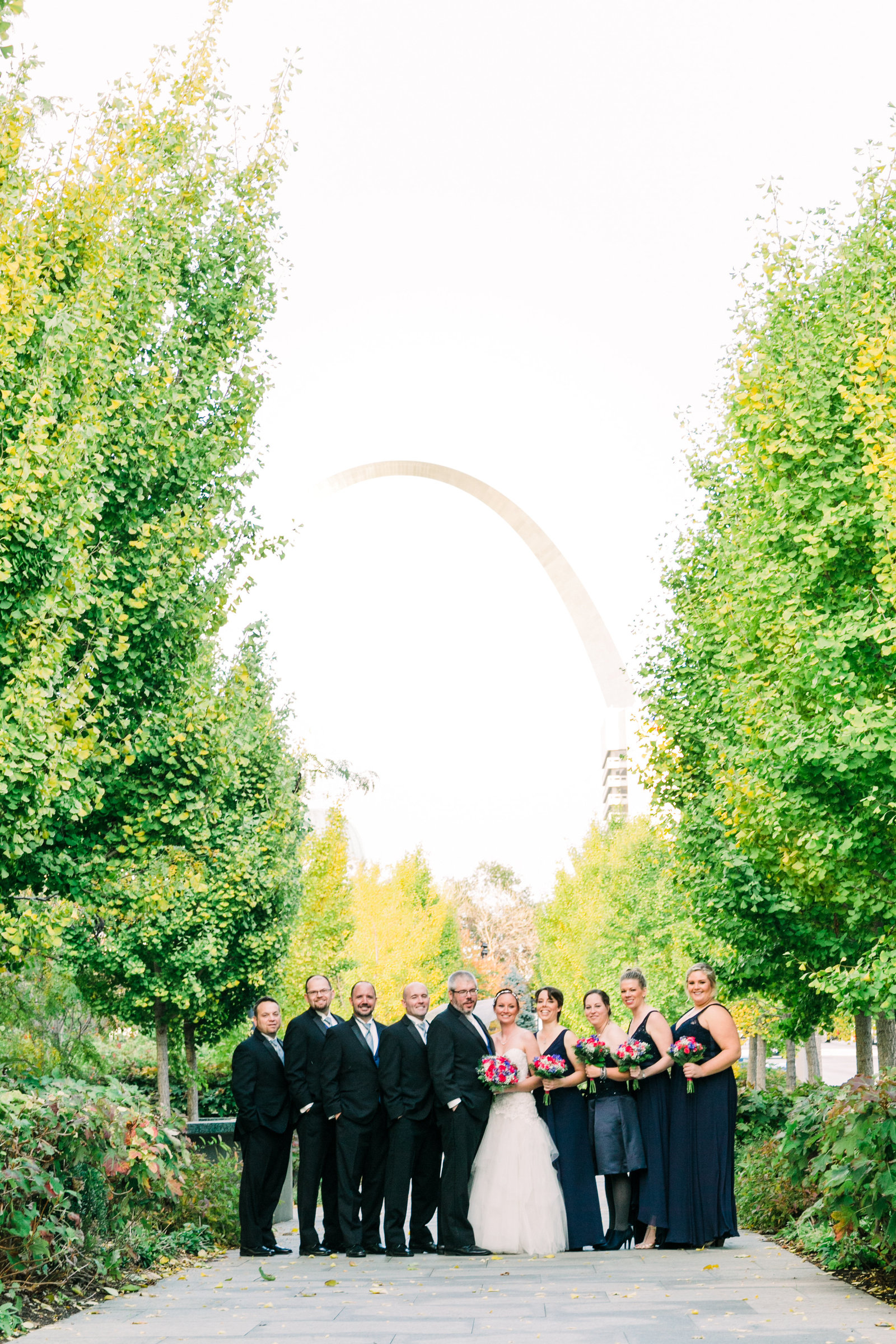 A Wedding party stands on a sidewalk in the St. Louis City Garden with the historic arch in the background