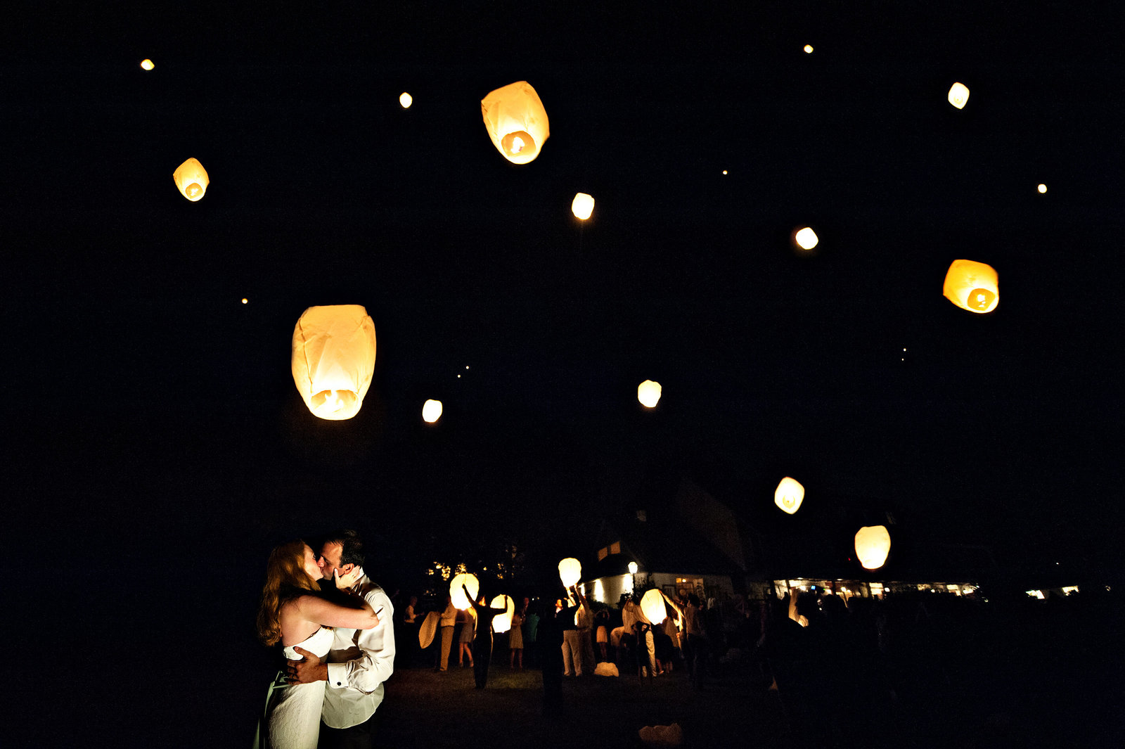 Wedding guests light paper lanterns  at the end of the wedding at Pheasant Run Farm.