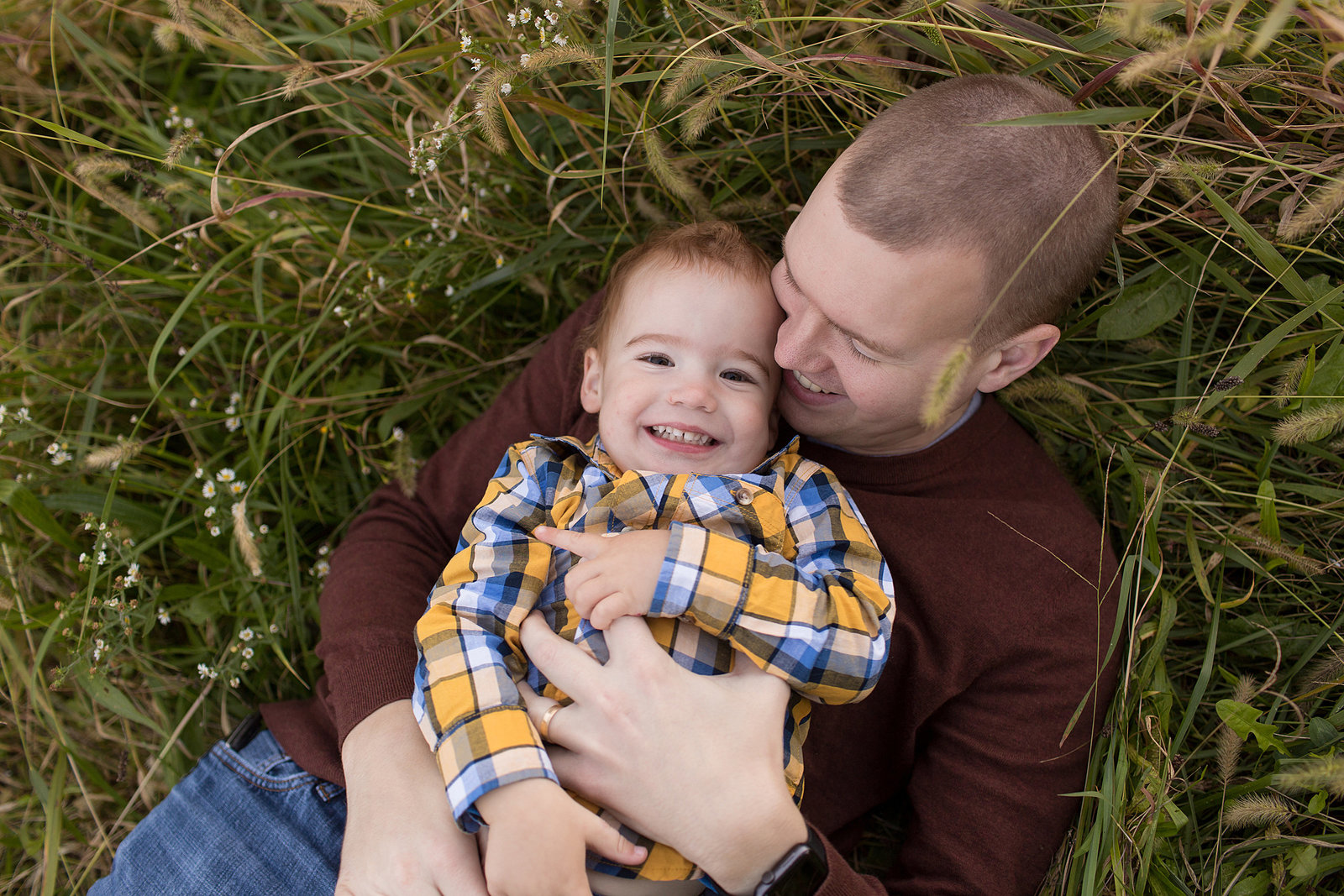 Dad tickles little smiling boy in long green grass