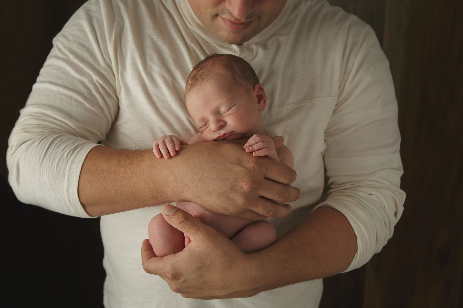 Hudson Valley NY professional newborn baby photographer captures new dad holding his infant son in Cornwall NY