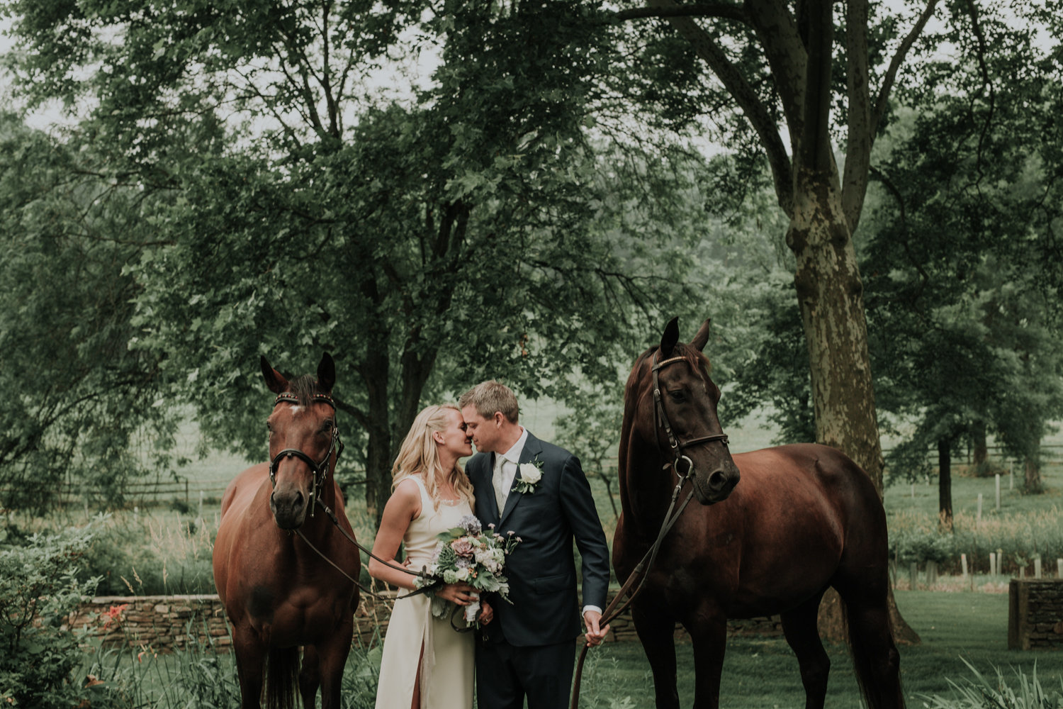 bride and groom pose with their horses at their PA farm wedding