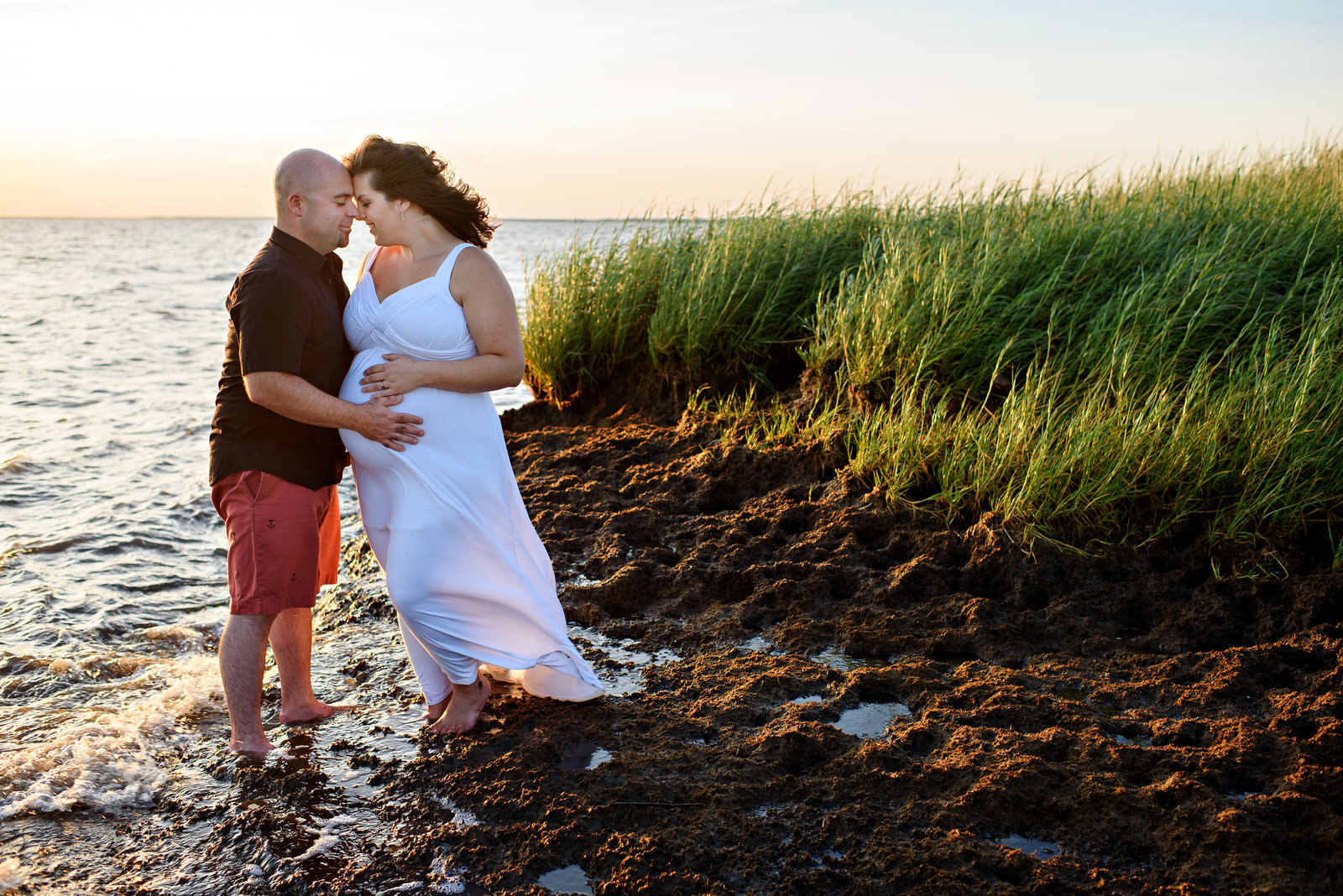 A pregnant couple stand in the water at the beach and hold each other.