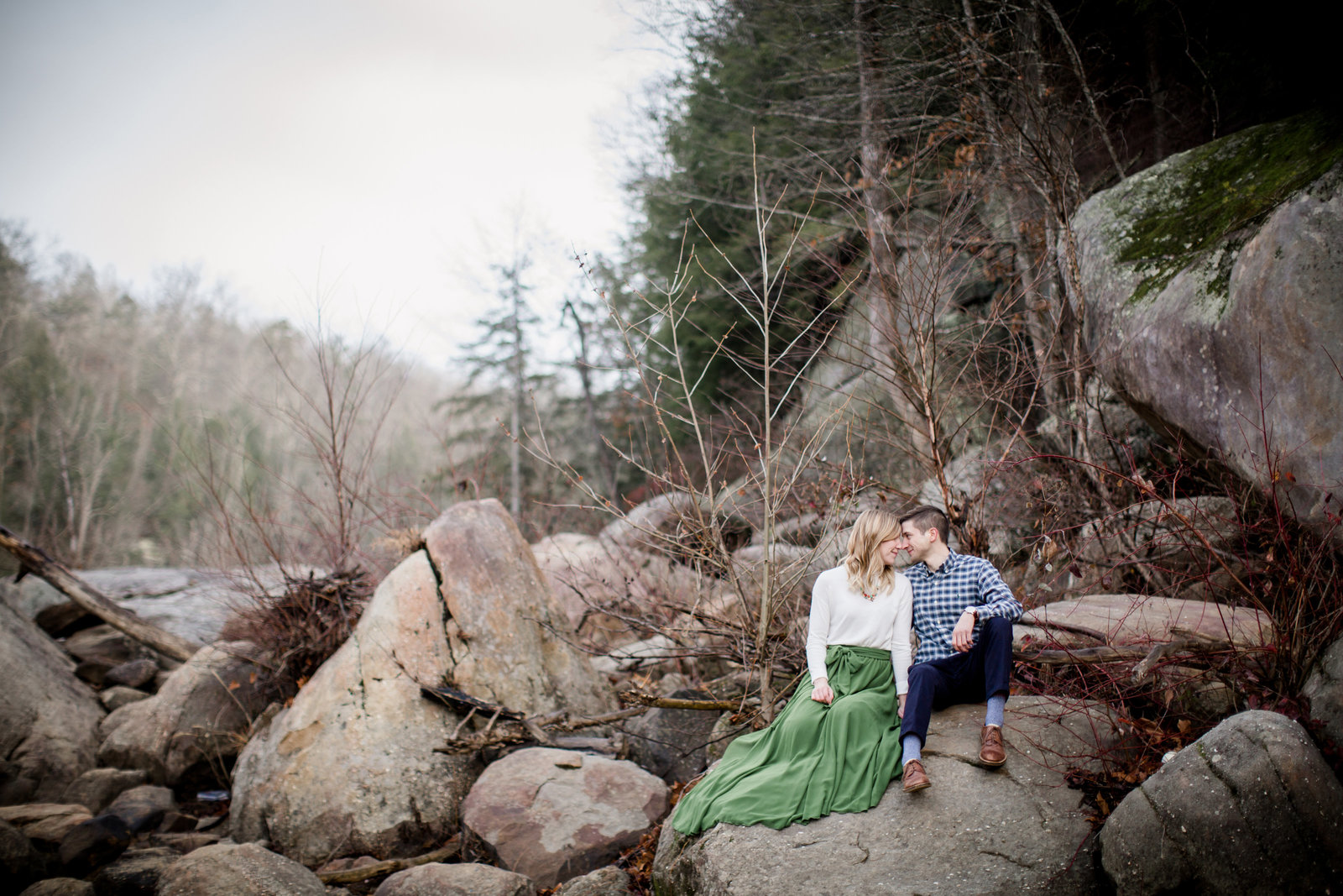 Sitting on big boulders at Cumberland Falls for their engagement session by Knoxville Wedding Photographer, Amanda May Photos.