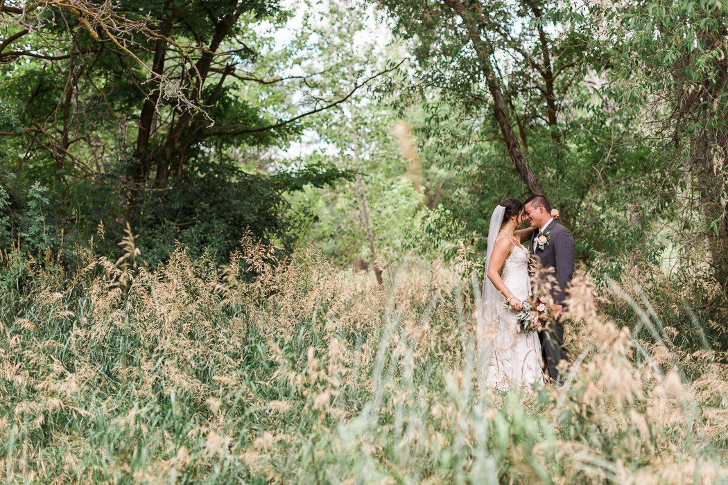 Bride and groom share a quiet moment in a lush meadow after their first look on their wedding day in Boise, Idaho.