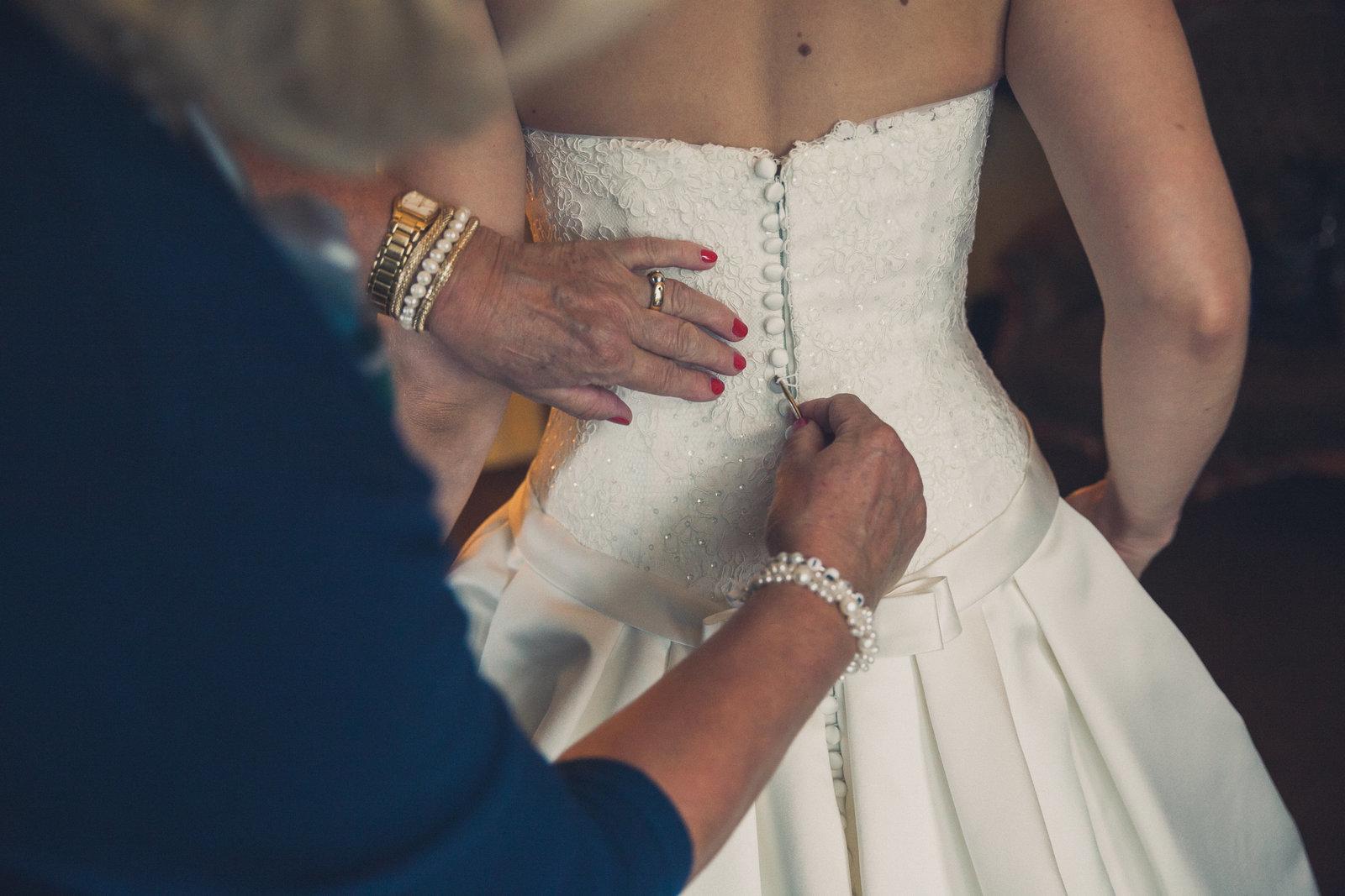 Knoopje, na knoopje! De moeder van de bruid maakt de trouwjurk van haar dochter dicht met een haaknaald. Copyright Nanda Zee-Fritse | FOTOZEE