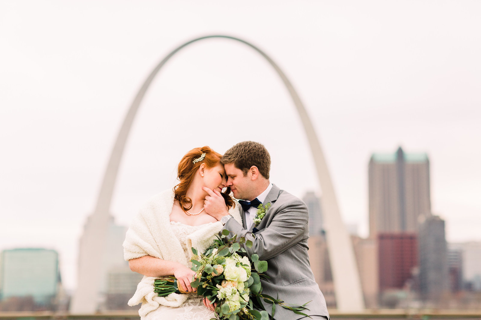 Bride and Groom, Kailyn and Adam, sit side by side leaning in for a kiss with the St. Louis Skyline and Arch in the background