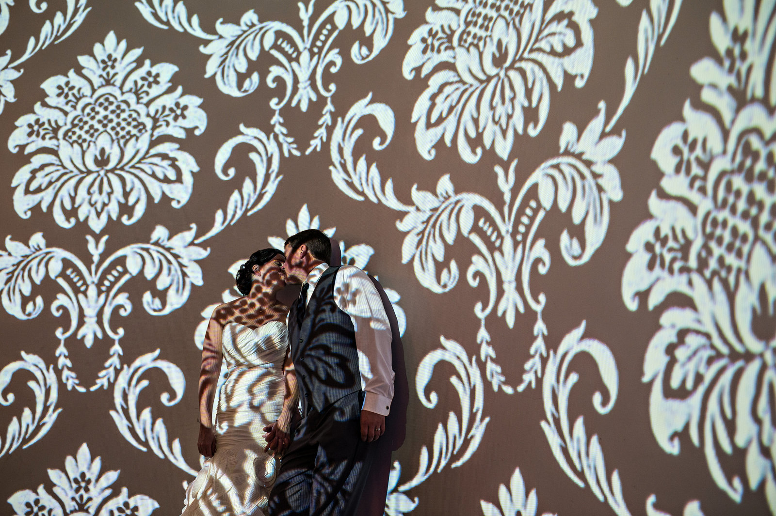A couple kiss in the light on the wall at their Vie Wedding in Philly.