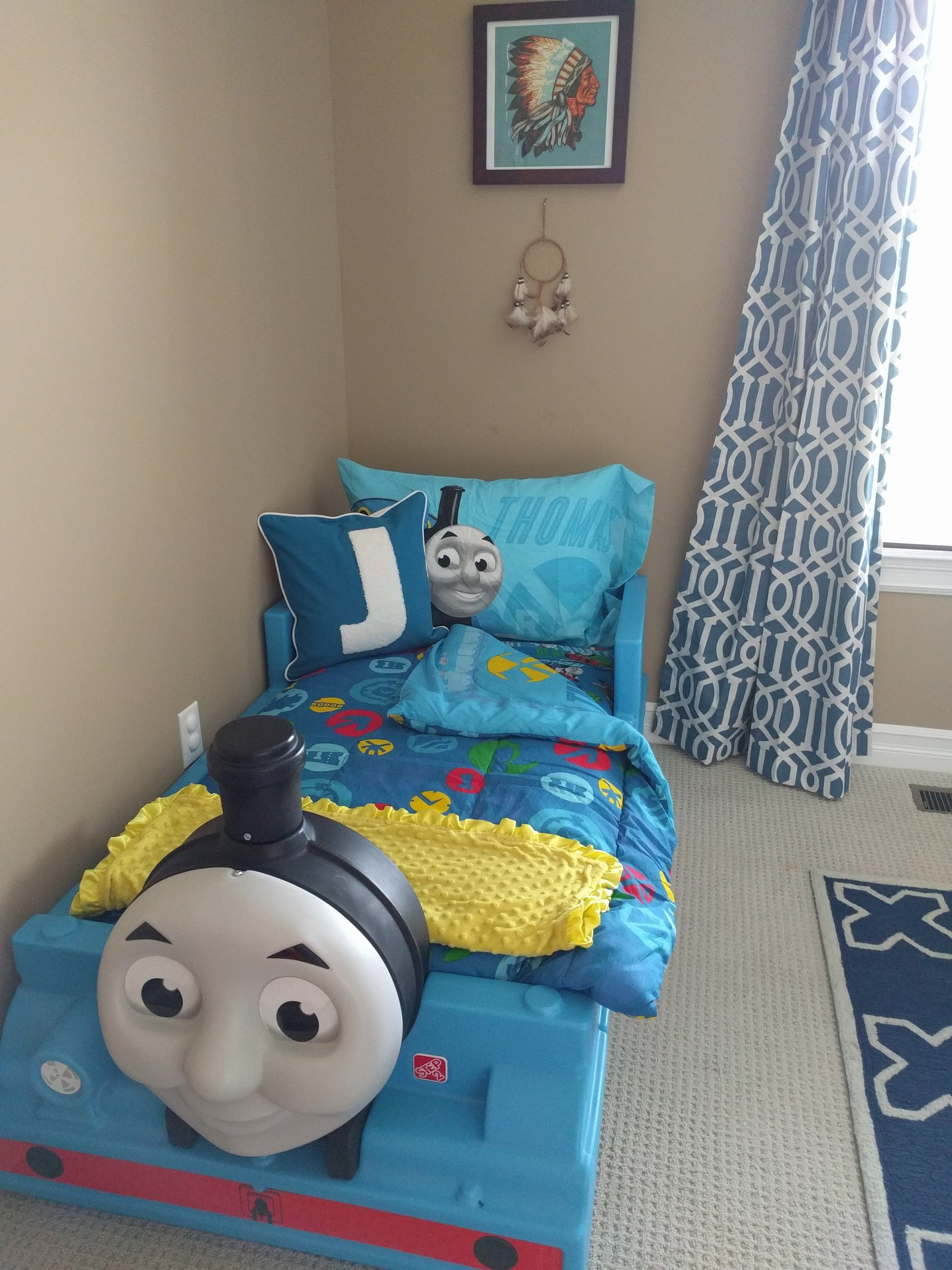 whimsical toddler boy bedroom with thomas the train bed