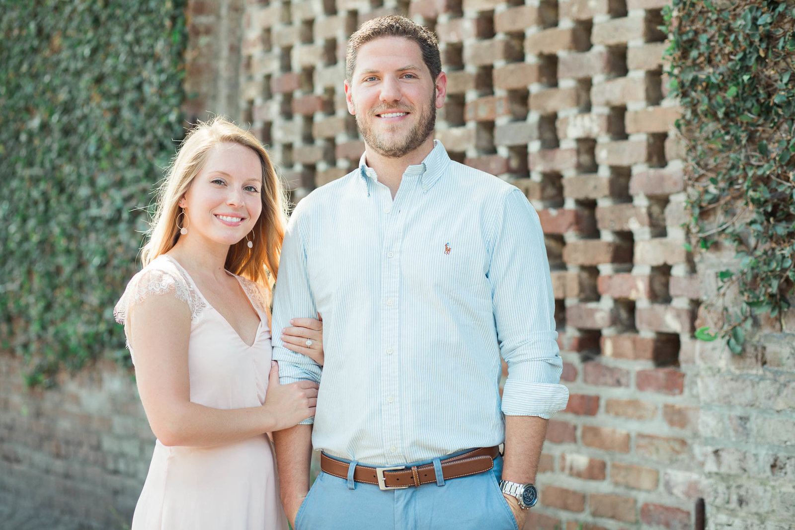 Engaged couple pose in front of red brick and ivy, Downtown Charleston, South Carolina