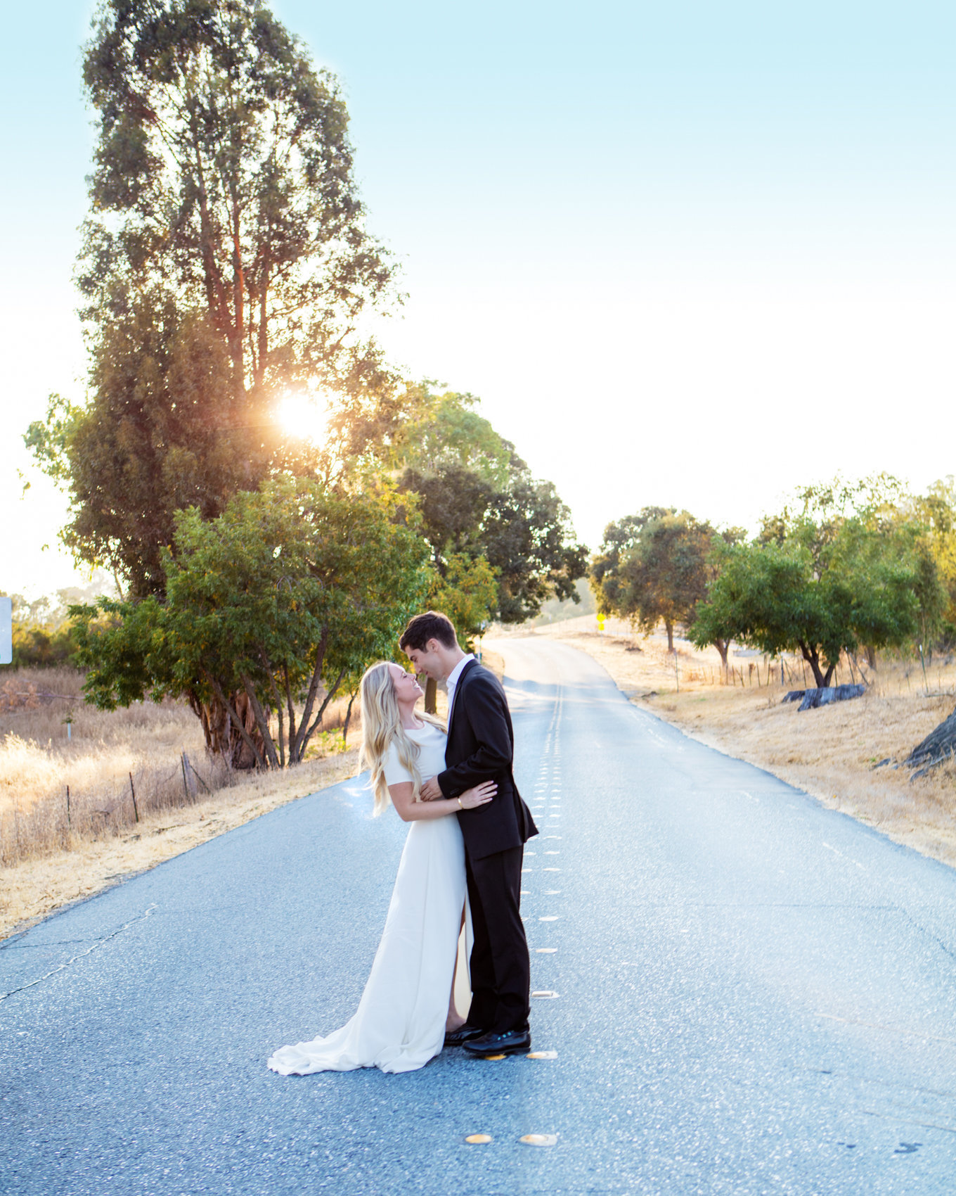 Northern California engagement session, bride and groom stands in street with golden hour lighting