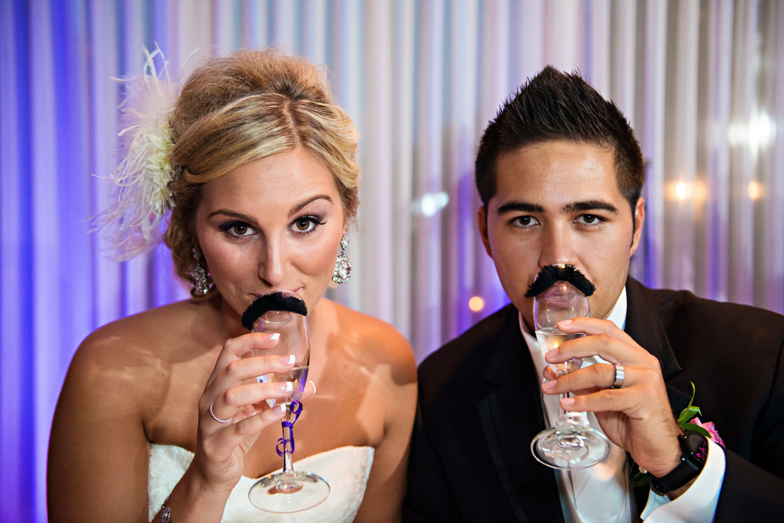 A bride and groom drink champagne from glasses with mustaches on them at their Northampton Valley Country Club Wedding.