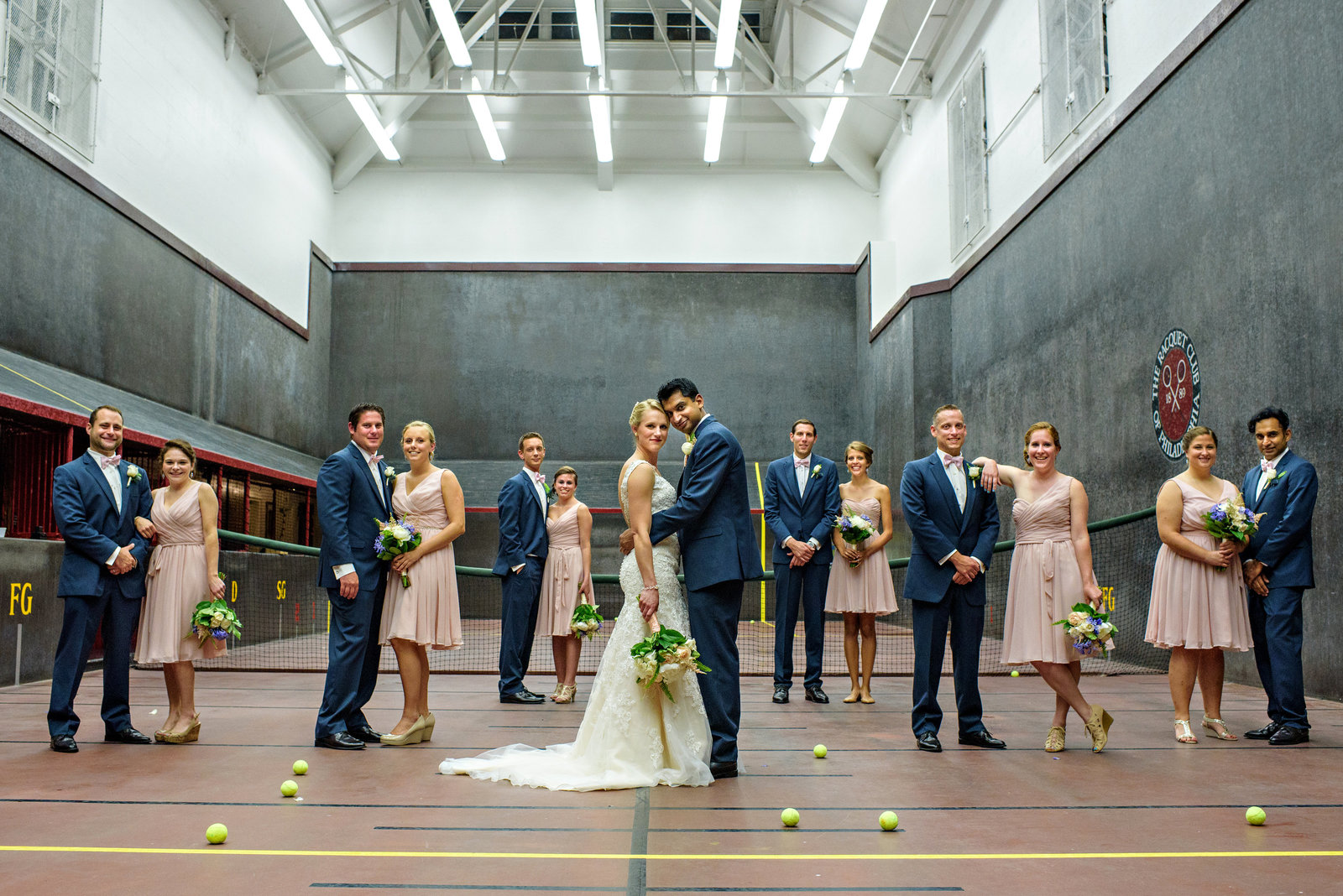A bridal party pose on a tennis court at the Racquet Club of Philadelphia.
