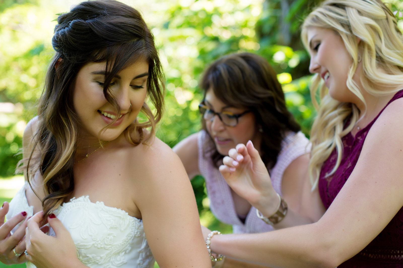 bride gets into her wedding dress outside at bridal veil lakes