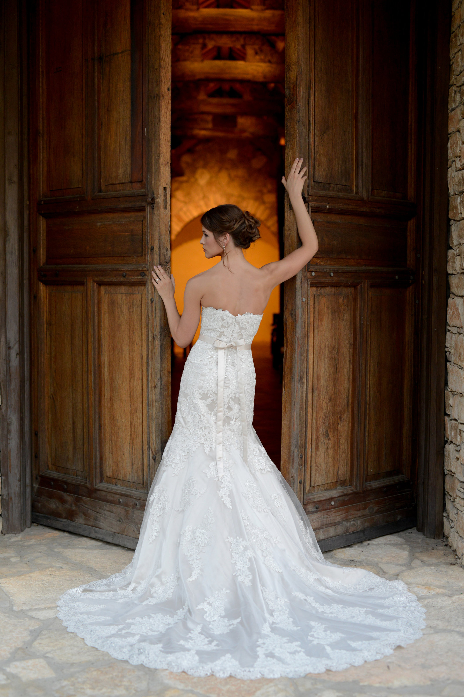 Bride holds onto door of Ian's Chapel in Dripping Springs; shows back of the Essence of Australia Wedding Gown with Pewter lining