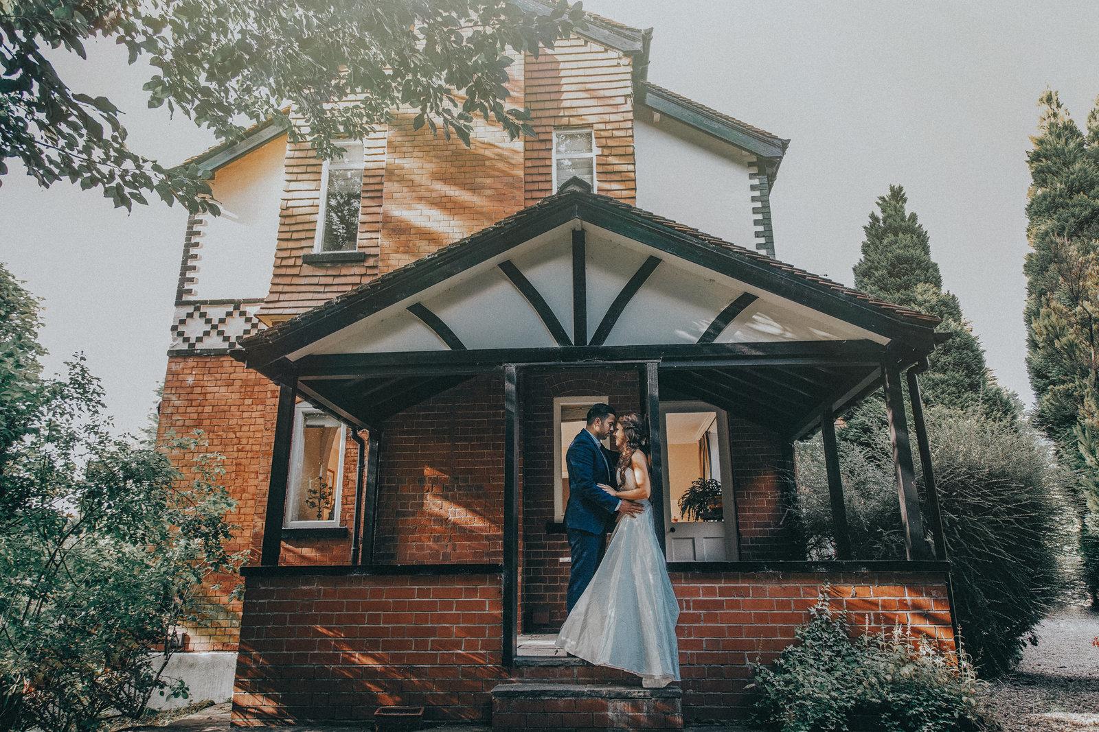 Bride & Groom kissing on porch f their home - Manchester Wedding Photographer Jono Symonds