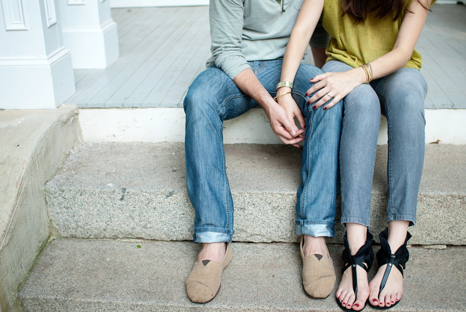 a couple holds hands on the front stoop of a house