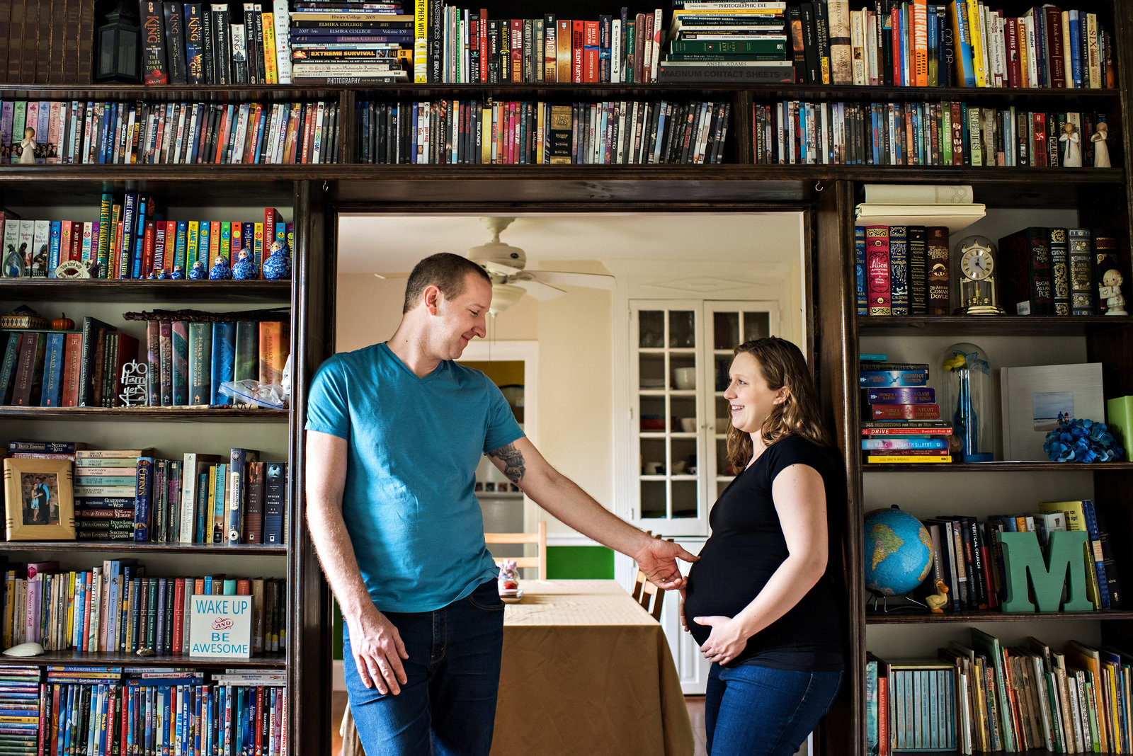 New parents to be stand under the bookshelf at their home and touch her pregnant belly.
