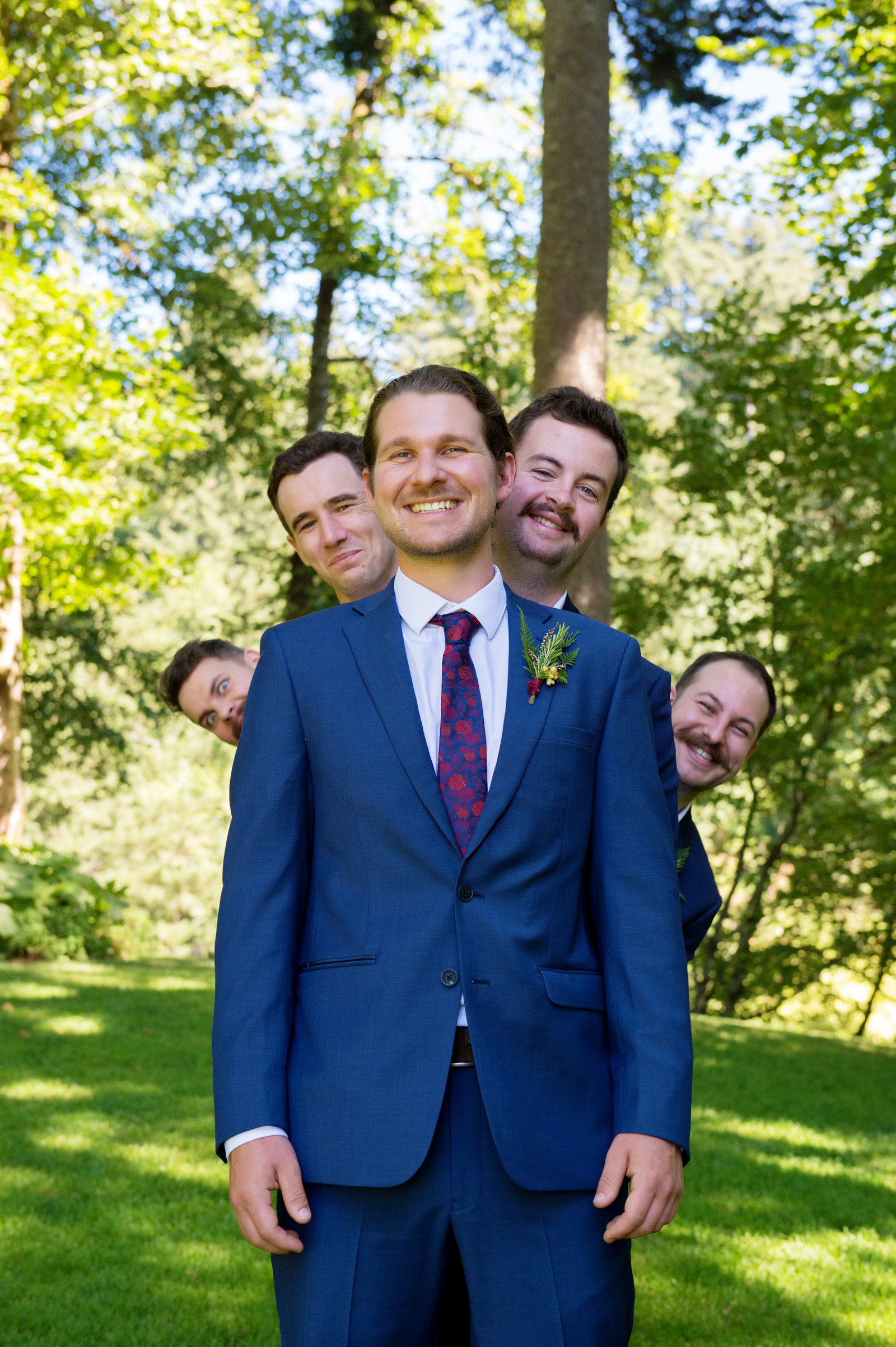 funny groomsmen peek out from behind the groom