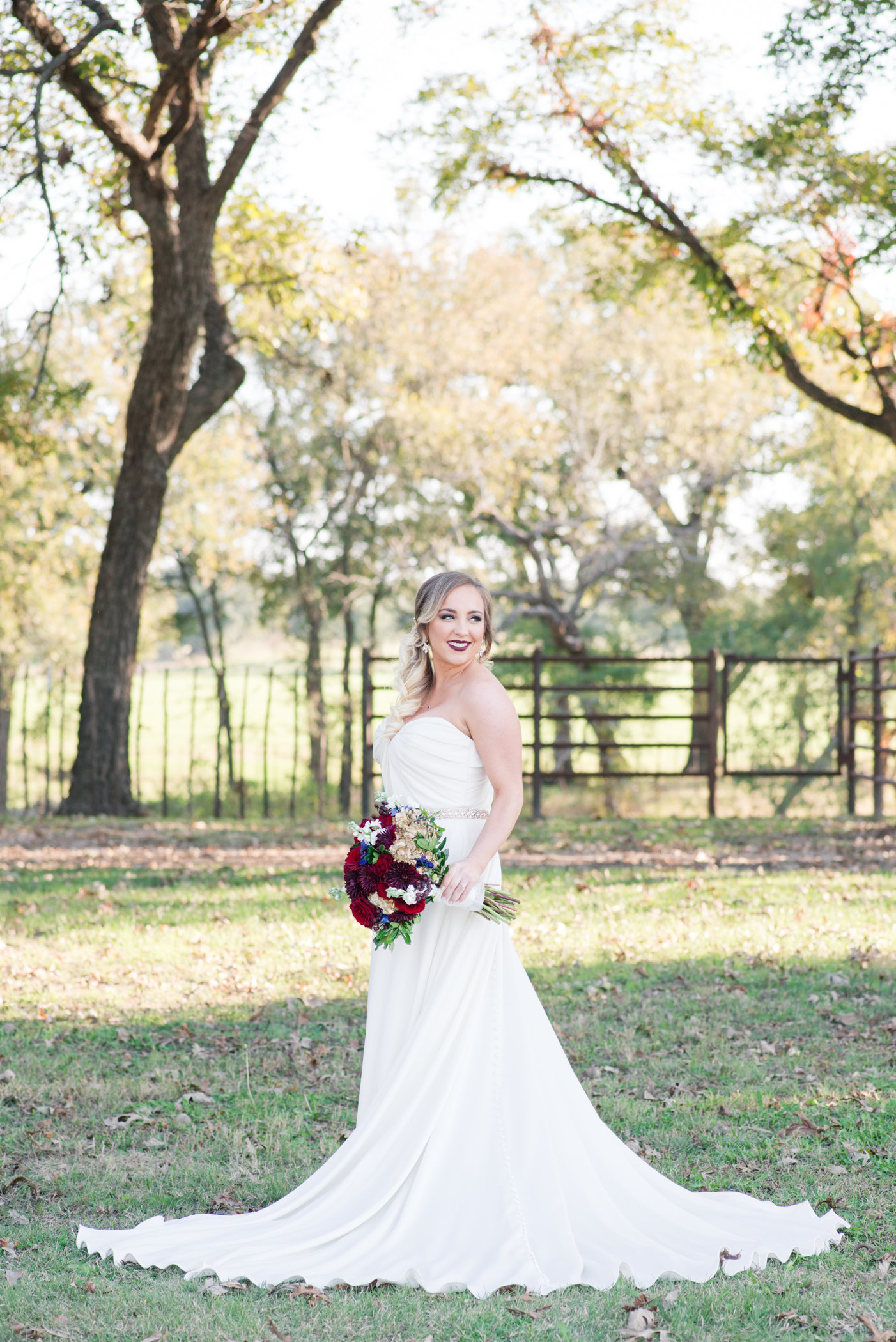 Bridal Portrait at The N at Hardway Ranch near granbury, Texas; Bride holds burgundy and gold wedding bouquet