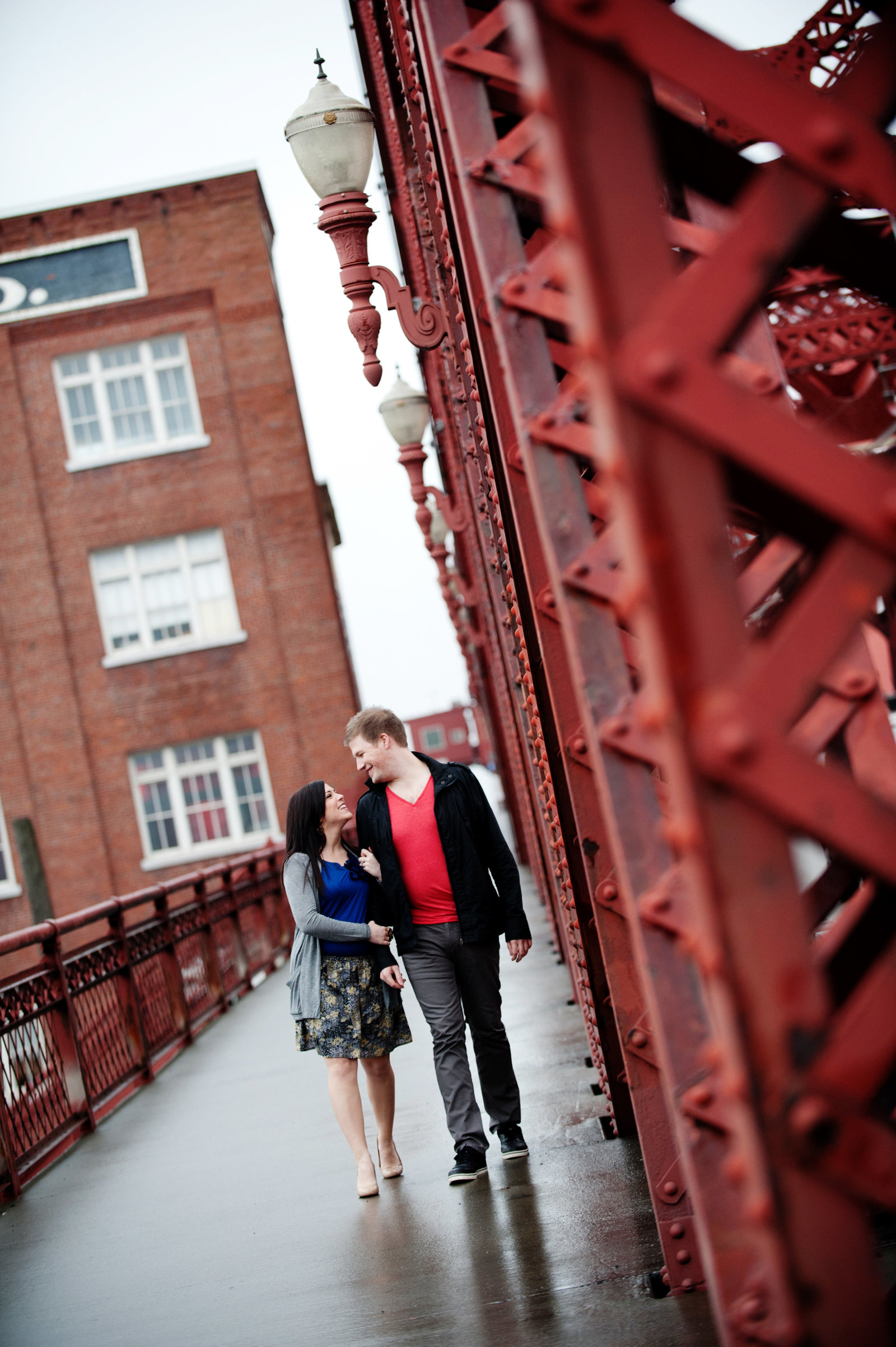 an engagement photo of a couple walking across the broadway bridge