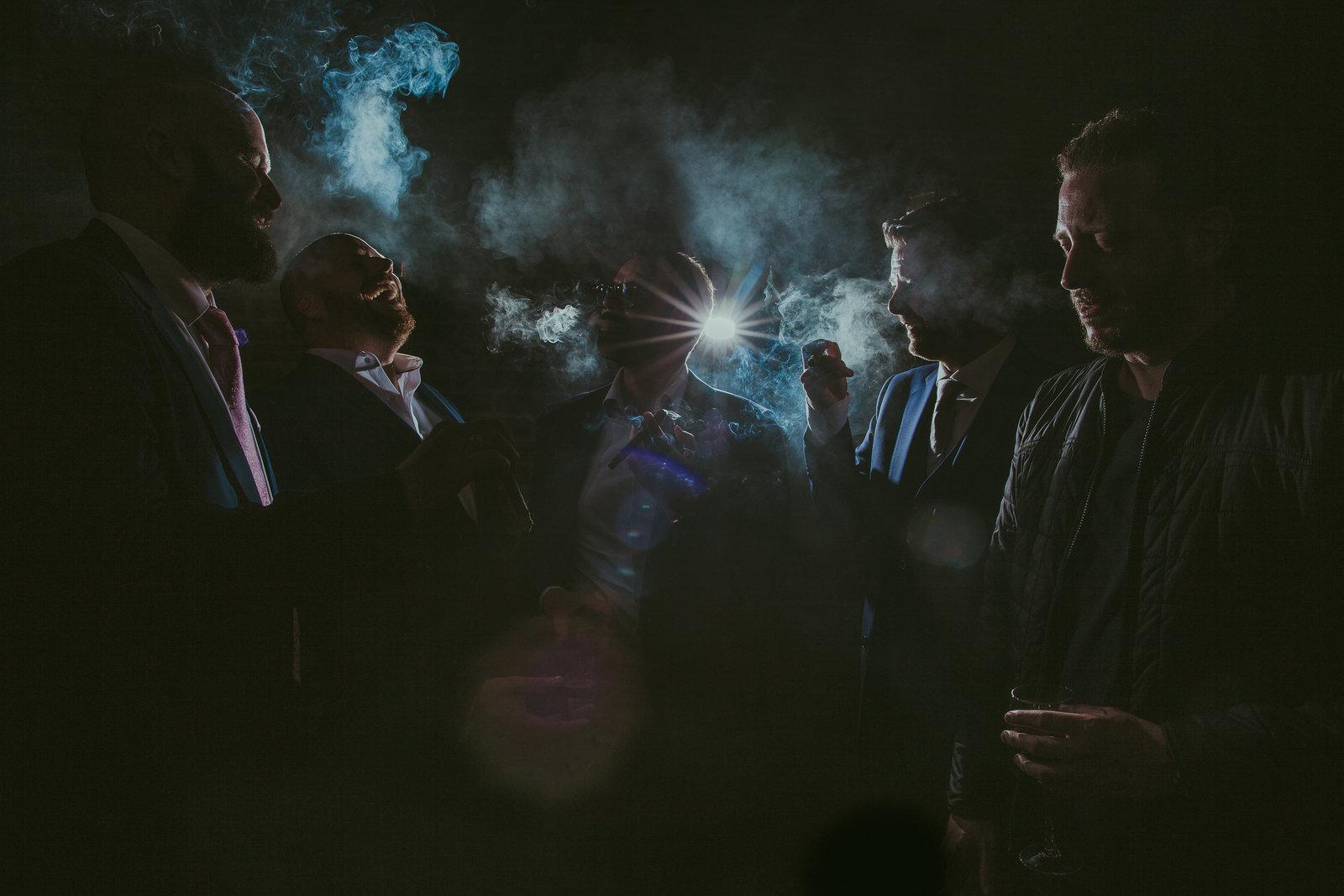 Kickass foto van bruidegom met zijn vrienden tijdens het roken van een sigaar. Smoking groom with friends. Strobe and smoke. Copyright Nanda Zee-Fritse | FOTOZEE