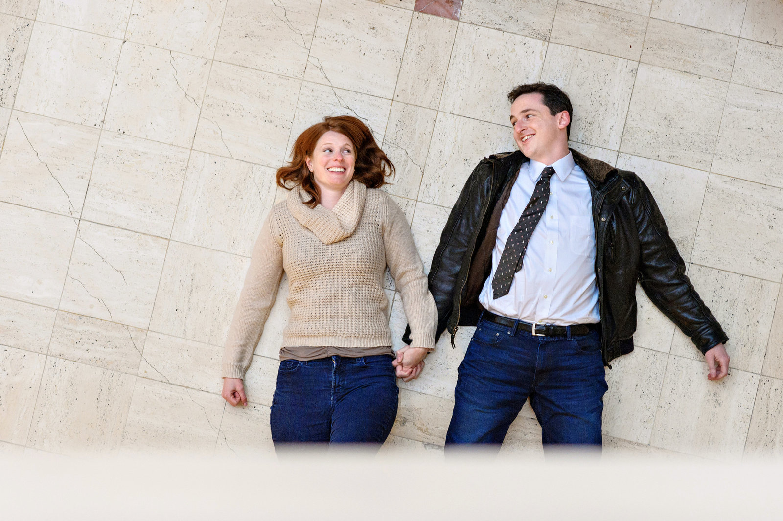 A funny couple lay on the floor of their hotel after a fun engagement session.