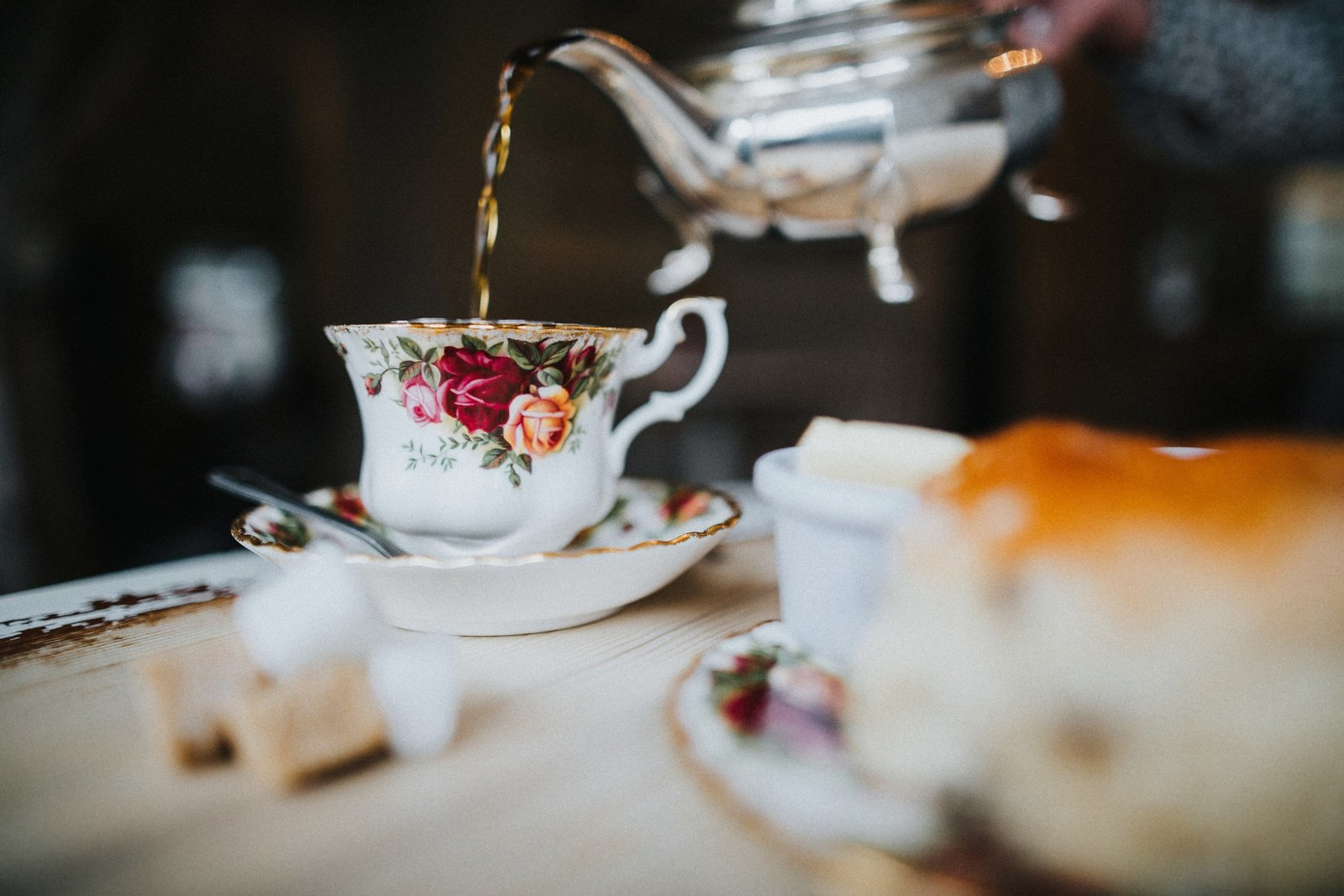 Tea being poured into vintage china teacup at Baldry's Tearoom in The Lake District