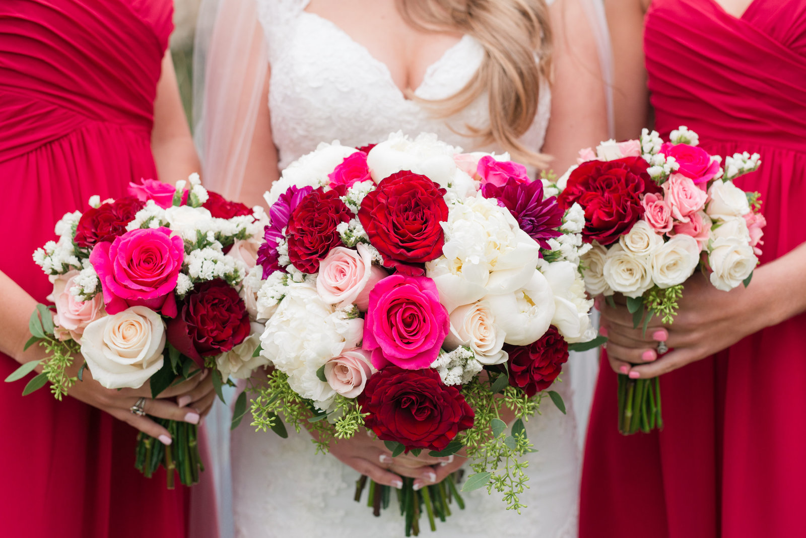 Bridesmaids in Cranberry dresses show their pink bouquets