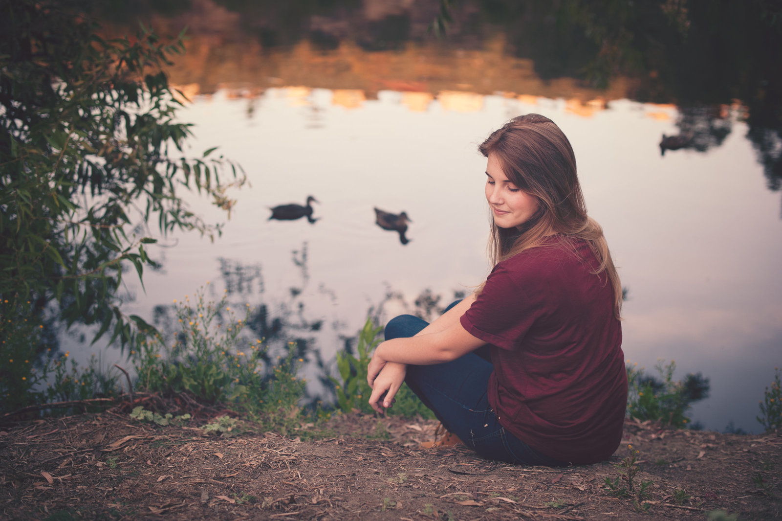 thoughtful teenager sitting by lake with ducks in Laguna Niguel Regional Park