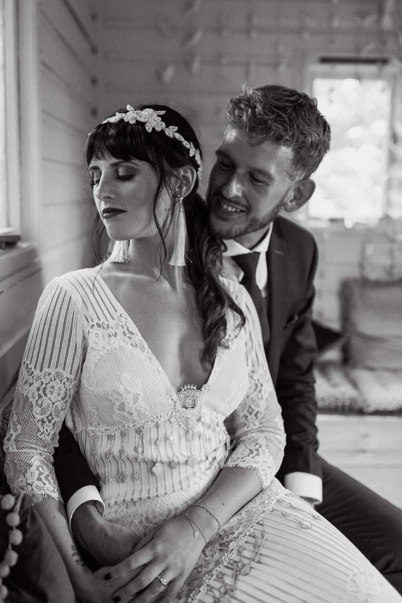 Vintage style photo of bride in Seville dress by Claire Pettibone with groom in Stephen Lawrence suit sat embracing and taking in the moment in the treehouse
