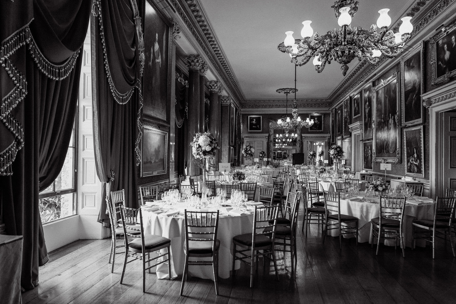 Black and white wedding photo of the grand ballroom at the Goodwood House wedding venue with draped curtains. chandelier and tall floral displays on round tables.